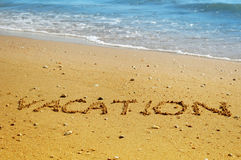 Vacation written in the sand. On the beach blue waves in the background Stock Photo