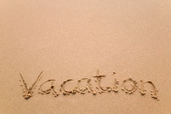 Vacation written in sand Royalty Free Stock Image