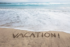 Vacation written in sand on a beach Stock Photo