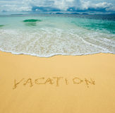 Vacation written in a sandy beach Stock Photos
