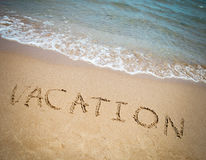 Vacation written in a sandy tropical beach Royalty Free Stock Image