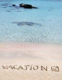 Vacation y comprobó la marca escrita en la arena en una playa hermosa, ondas del azul en fondo Foto de archivo