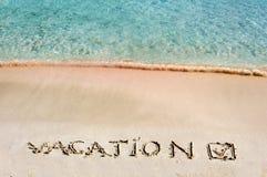 Vacation y comprobó la marca escrita en la arena en una playa hermosa, ondas del azul en fondo Fotos de archivo libres de regalías