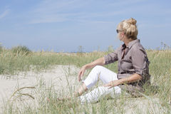 Vacationer sitting on the beach Stock Photography