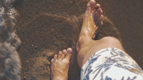 Vacationer walking along the sea coast and waves washing his feet. Top view of barefoot man vacationer walking along the beach and sea waves washing his feet stock video