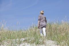 Vacationer walking through dunes Royalty Free Stock Image