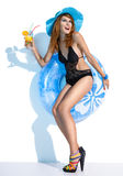 Vacationer young woman. Attractive brunette girl of the European appearance with refreshing beverage in her hand holds an inflatable circle Stock Images