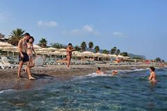 Vacationers basking in seawater on beach with parasols and deckc Royalty Free Stock Images