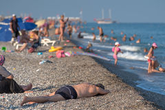 Vacationers bathe in the sea and sunbathe on gravel beach. Stock Image