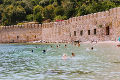 Vacationers bathe and sunbathe against the background of the ancient fortress wall Alanya, Turkey Stock Images
