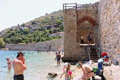 Vacationers bathe and sunbathe against the background of the ancient fortress wall Alanya, Turkey Royalty Free Stock Photography
