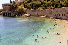 Vacationers bathe and sunbathe against the background of the ancient fortress wall Alanya, Turkey Royalty Free Stock Photos
