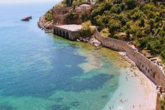 Vacationers bathe and sunbathe against the background of the ancient fortress wall Alanya, Turkey Stock Photography