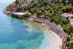 Vacationers bathe and sunbathe against the background of the ancient fortress wall Alanya, Turkey Stock Photo