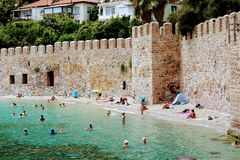 Vacationers bathe and sunbathe against the background of the ancient fortress wall Alanya, Turkey Royalty Free Stock Photo