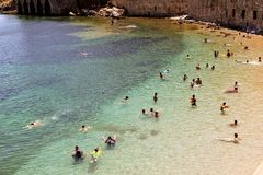 Vacationers bathe and sunbathe against the background of the ancient fortress wall Alanya, Turkey Stock Image