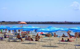 Vacationers on the beach. And crowded pier in the opposite-the swimming marathon Galata - Varna final point,Varna ,Bulgaria Royalty Free Stock Photo