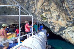 Vacationers on cruise boat. Vacationers  look exited ahead to the  tourist attraction Papanikolis cave on cruise ship deck ,during World War II  being a secret Stock Image