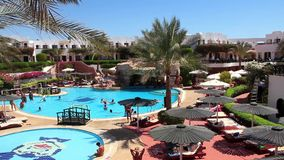 Vacationers. EGYPT, SOUTH SINAI, SHARM EL-SHEIKH, SEPTEMBER 22, 2010: People in hotel area with swimming pool in Sharm El Sheikh, Egypt, September, 22, 2010 stock footage