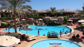 Vacationers. EGYPT, SOUTH SINAI, SHARM EL-SHEIKH, SEPTEMBER 22, 2010: People in hotel area with swimming pool, Sharm El Sheikh, Egypt, September, 22, 2010 stock video