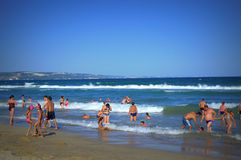 Vacationers enjoy sea waves Stock Images