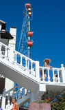 Vacationers. A girl in a bikini and hat is standing on the stair Stock Image