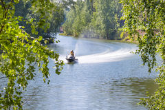 Vacationers go on a water bike in a small Siberian river Stock Images