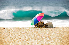 Vacationers at the Hawaiian beach. A couple of vacationers at the Hawaiian beach watching a big wave approaching the shore Stock Image