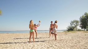 Vacationers playing volleyball on the beach.