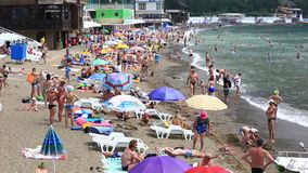 Vacationers on a public beach, Novy Svet, Crimea. People relax by the sea on the beach, Novy Svet, Crimea stock video