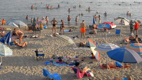 Vacationers relaxing at beach and bathing in sea, Greece. Nea Kallikratia, Greece - August 12, 2017: crowded beach with people relaxing on the sand and bathing stock video