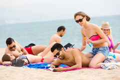 Vacationers sunbathing near ocean Stock Images