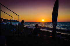 Vacationers On The Sunset Shore Stock Photos