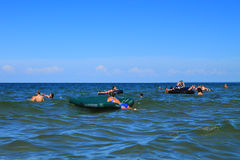 Vacationers swim on air mattresses on shoal in the Baltic Sea Royalty Free Stock Photo