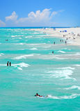 Vacationing Crowd on Beach. Beautiful ocean water with swimmers and surfers vacationing on beach Stock Photo