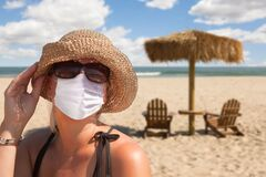 Free Vacationing Woman Wearing Face Mask On Sandy Beach Royalty Free Stock Images - 175122729