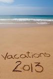Vacations 2013 written in sand on tropical beach stock photo