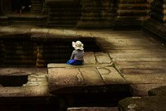 Little girl sitting resting in Angkor Wat royalty free stock photo