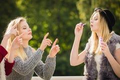 Women friends blowing soap bubbles. Royalty Free Stock Image