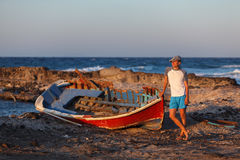 Vacations on Santorini. Young man standing near the old broken boat and looking at sunset Royalty Free Stock Photo