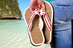 Vacations Start. Girl holding sandals on the first day of vacations at the beach Stock Photography