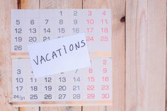 Free Vacations Written On Paper Note On A Wall Calendar Stock Photo - 128767420