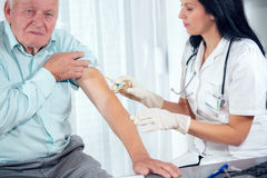 Vaccinating An Elderly Person. Female nurse and senior man Stock Photography