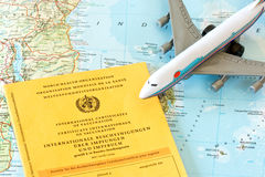 Vaccination card on a map. Toy airplane with vaccination card on a map Stock Photography