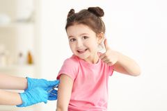 Vaccination concept. Female doctor vaccinating cute little girl. In clinic royalty free stock photos