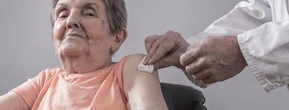 Vaccination d'une femme agée images libres de droits
