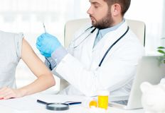 Vaccination. Flu shot. Doctor injecting flu vaccine to patient`s arm royalty free stock images