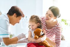 Vaccination to a child. A doctor making a vaccination to a child. Kid with mother royalty free stock photography