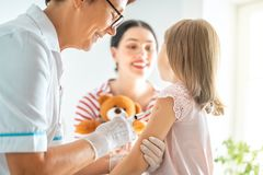 Vaccination to a child. A doctor making a vaccination to a child. Kid with mother royalty free stock photo