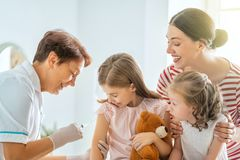 Vaccination to child. A doctor making a vaccination to a child. Kids with mother royalty free stock photos